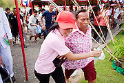 13 MAY 2010 - BANGKOK, THAILAND: People rush onto the field after the Royal Plowing Ceremony to gather up rice seeds that have been blesses by Brahman priests. The Royal Ploughing Ceremony dates back to at least the Sukhothai Period (ca 13th and 14th centuries). The event is a Brahman ceremony. In ancient times it was to portend the agricultural fortunes of the coming planting season, bless the fields and pray for bountiful rains. Now it is more of a cultural event the Thai monarchy, which presides over the event, uses to stress the importance of farming to the nation. However, people still flock to it for the religious aspects and afterwards try to gather rice seeds, which have been blessed by the Brahman priests. Thailand is experiencing its worst drought in decades this year and despite the prayers of the priests Thai farmers are being told to expect smaller yields. They are being asked to delay planting for up to a month to use less water.  PHOTO BY JACK KURTZ