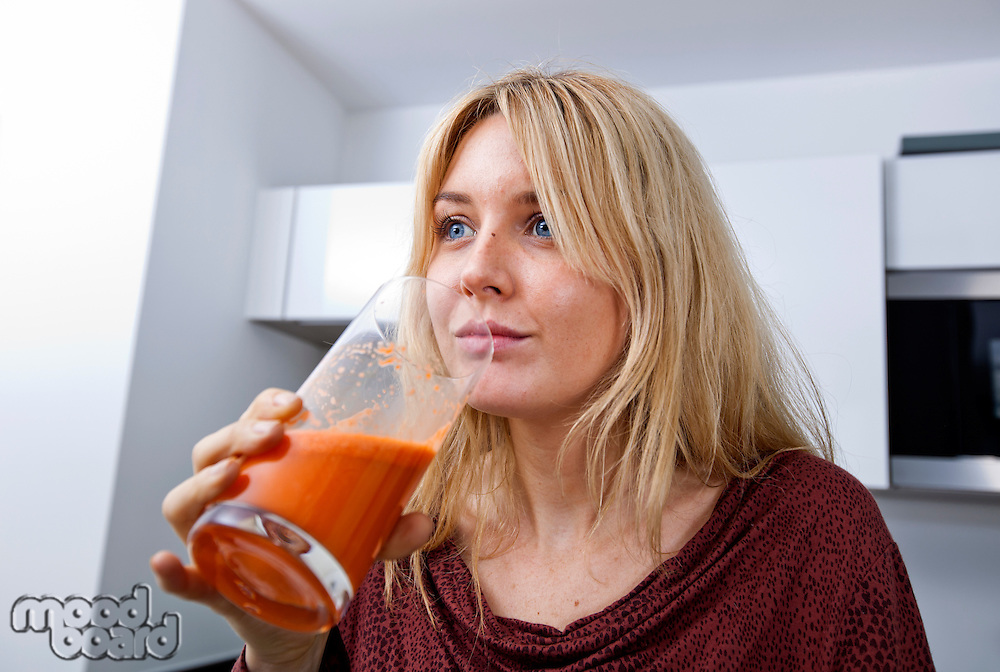 Young woman drinking carrot juice in kitchen