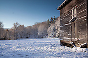 A snowy shed at the edge of a meadow after an ealy snowfall