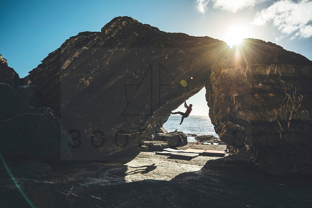 Silhouette of a climber climbing in a overhanging boulder problen close to the sea Mamut climbing athlete Bobbi Bensman enjoying a climbing trip at Roca Verde, Asturias, Spain