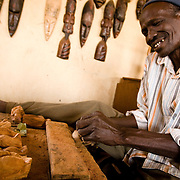 A man makes wooden carvings at the Village Artisanal de Ouagadougou, a cooperative that employs dozens of artisans who work in different mediums, in Ouagadougou, Burkina Faso, on Monday November 3, 2008.