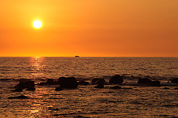 The setting sun at sunset as seen from the Keauhou Beach Resort next to Kahaluu Beach Park in Keauhou on the Big Island of Hawaii. In the foreground are the remains of an ancient breakwater known as Paokamenehune or menehune breakwater that was built by ancient Hawaiians.