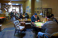 Old men playing cards at card table at 9:00am on a weekend morning at Pappa Joe's Restaurant in Ferndale, California