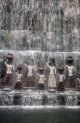 Statues of women holding jars standing under waterfall in rock garden at Chandigarh; Punjab; India,