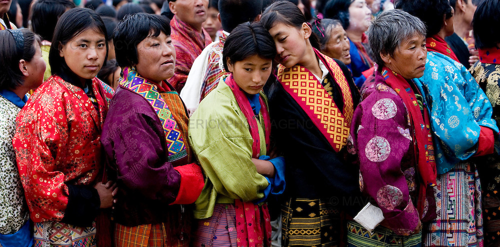 A young woman whispers to her friend as women queue up  to get blessed by monks at the unveiling of the Thangka (religious mural) of Guru Rinpoche in the final event of the Paro festival at Rinpung dzong, Paro...Commonly described as the last Himalayan Shangrila, Bhutan is a country of unique serenity, harmony, and beauty. Nestled between India, China, and Tibet, this independent country whose name translates as 'the Land of the Thunder Dragon' has for the past 300 years  proactively followed a policy of isolation and cultural protection. Travel in and out of the country is strictly regulated, and the impact of outside influences on the local culture is carefully monitored. Spirituality is an important aspect of Bhutanese culture, with Buddhism being interlinked with everyday life. Gross National Happiness (GNH), as opposed to GNP/GDP, forms the cornerstone of its development strategy which focuses on a holistic development strategy that complements its cultural and Buddhist spiritual values.