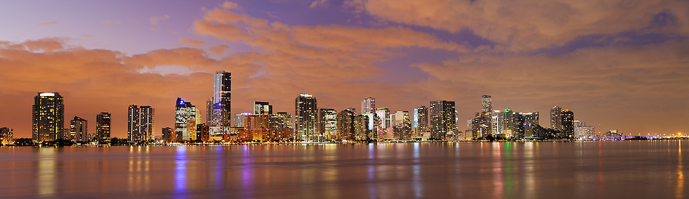 Panoramic view of the downtown Miami, Florida bayfront skyline at night, showing hotels, condos and office buildings, as well as bridges and part of the Port of Miami. WATERMARKS WILL NOT APPEAR ON PRINTS OR LICENSED IMAGES.
