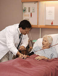 doctor visiting senior woman patient in hospice
