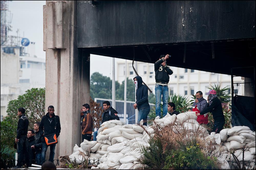 Des manifestants sont rassemblés place de Barcelone dans le centre de Tunis lors d'affrontements avec les forces de police. // Des affrontements entre la police et les manifestants ont éclaté dans le centre de Tunis, notamment avenue Habib Bourguiba, faisant (selon Associated Press) 3 morts (prétendument par balle) et 12 blessés parmi les manifestants, Tunis le 26 février 2011.