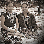 Traditionally dressed Navajo women wearing traditional jewelry with corn grinding stone