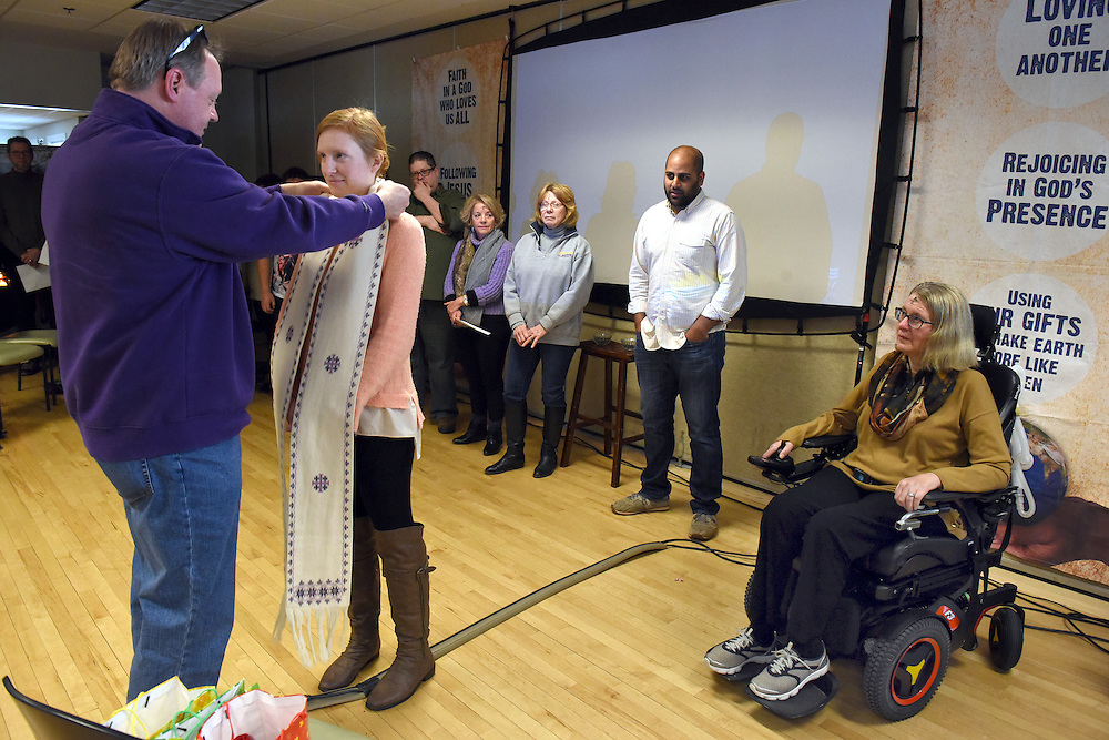 Mara Lavitt -- Special to the Hartford Courant<br /> February 14, 2016, Glastonbury<br /> Amyotrophic Lateral Sclerosis (ALS) forced Nancy Butler of Marlborough, right, to step down as pastor of the Riverfront Family Church in Glastonbury during the Sunday service. Three co-pastors will take over for her including her daughter Liza Arulampalam of Hartford, center, who receives a stole from her father Greg Butler, left. The stole belonged to Nancy who received it from a mentor.
