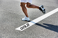 Man running on white line with gold winner sign