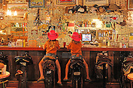 Two girls in saddle at Superstition Saloon Mercantile, Apache Trail, Tortilla Flats, Arizona, USA