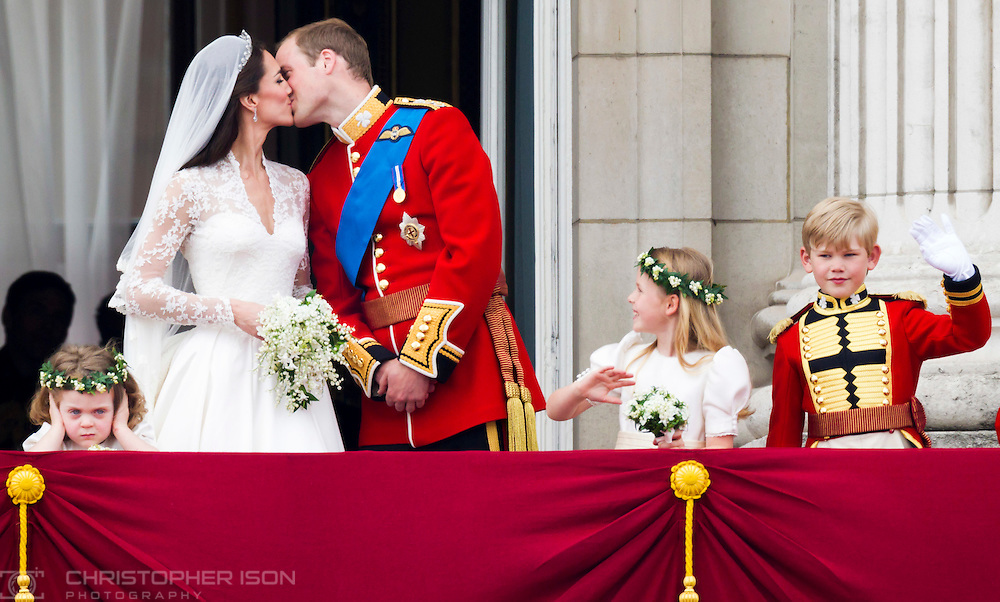 Prince William and his wife Kate Middleton, who has been given the title of The Duchess of Cambridge, kiss on the balcony of Buckingham Palace, London watched by bridesmaids Margarita Armstrong-Jones (right) and Grace Van Cutsem (left), following their royal wedding at Westminster Abbey. Photography by Christopher Ison