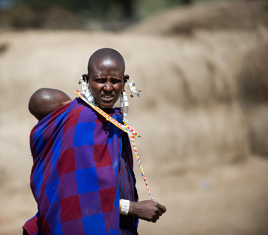 Maasai woman carrying baby on back