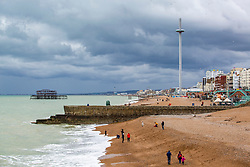 © Licensed to London News Pictures. 09/11/2019. Brighton, UK. Dark clouds hang over Brighton and Hove as members of the public brave the cold weather and head out to the beach. Photo credit: Hugo Michiels/LNP