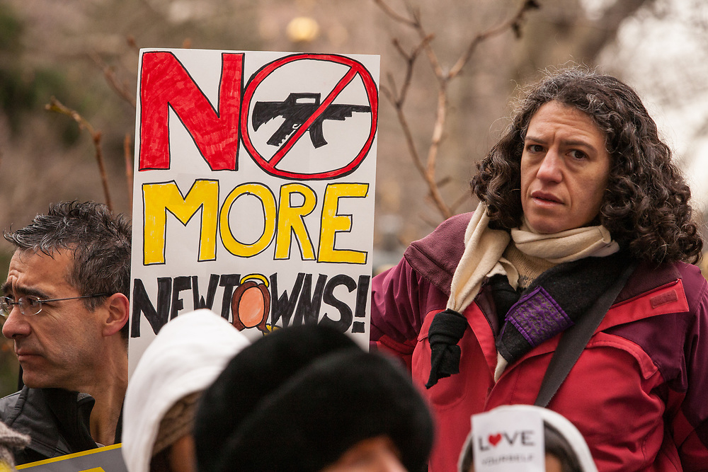 "A woman with a placard reading ""No more Newtowns."""