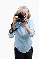 Senior female photographer using camera against white background