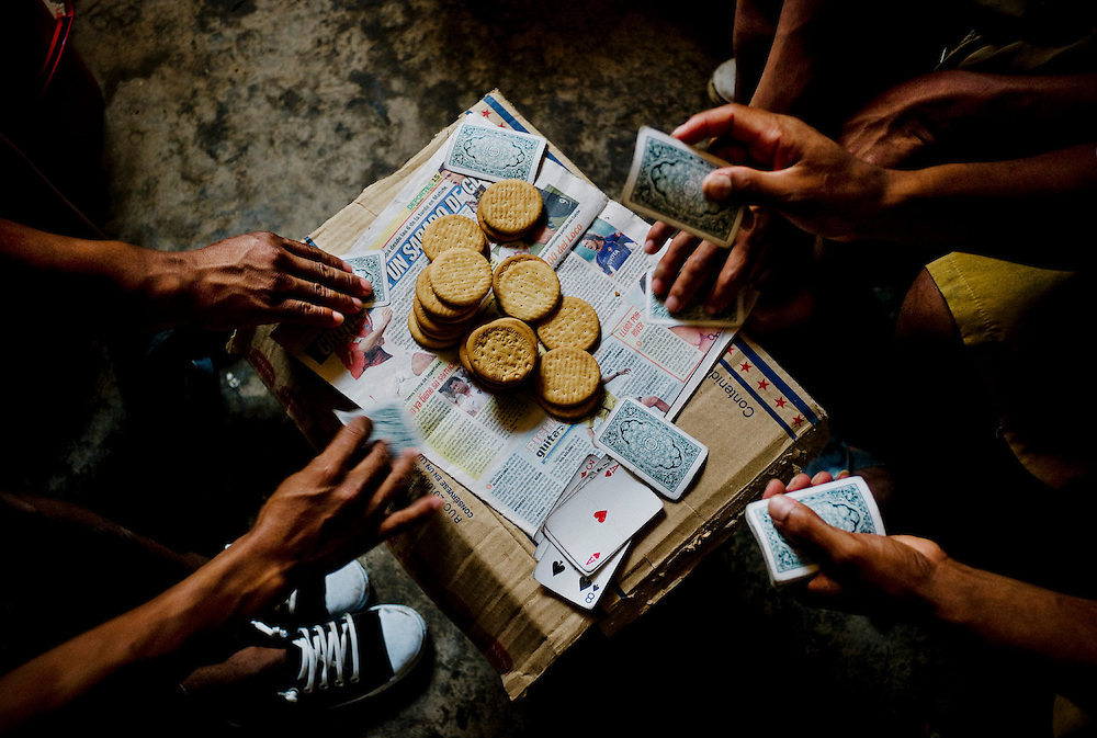 "Laborers play ""golpeado"" betting the biscuits they get from their company at their dormitories in Guañape Norte Island in the coast off Peru, April 2009."