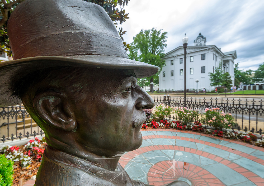 "A bronze statue of William Faulkner looks out over Courthouse Square, May 31, 2015, in Oxford, Mississippi. In the background is the Lafayette County Courthouse, which played a frequent role in his novels — so much so that a plaque on an outer column contains a quote from ""Requiem for a Nun"": ""But above all, the courthouse: the center, the focus, the hub; sitting looming in the center of the county's circumference … protector of the weak, judiciate and curb of the passions and lusts, repository and guardian of the aspirations and the hopes …"" (Photo by Carmen K. Sisson/Cloudybright)"