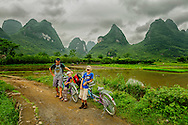 A family bicycling in the karst formation of Yulong River valley, Yangshuo, China