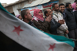 Demonstrators singing songs against the regime of Bashar-al-Assad with a free Syrian flag in Adanan, 8 kilometers north from Aleppo, north Syria, thursday, April 19, 2012...*In this town, 10 persons have been found dead,15 wounded and one missing in an attack were 18 tanks, 14 military cars and arround 300 soldiers burned down 118 houses and 120 shops in a operation by the Syrian regime of Bashar-Al-Assad at April 13th and 14th activist says, Syria, April 19, 2012. Photo by Daniel Leal-Olivas / i-Images.