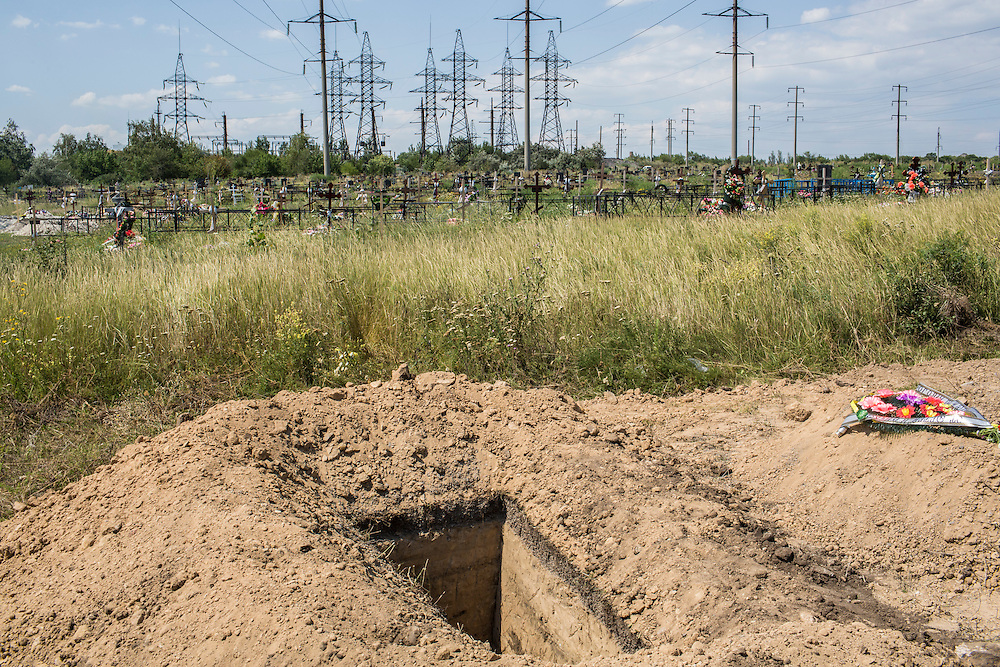 The grave of Vladimir Mitrofanovich Fkhorikh, a janitor who was killed when a shell exploded near him outside the apartment building where he worked, on Thursday, July 31, 2014 in Donetsk, Ukraine. Fkhorikh and his family had fled to Donetsk to escape fighting in his hometown, near the former rebel stronghold of Slovyansk.