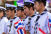 "24 JULY 2014 - BANGKOK, THAILAND: Thai Sea Scouts carry Thai flags in a patriotic parade at the happiness party in Bangkok. The Thai Junta is organizing a series of public events throughout Thailand meant to bolster public opinion. The events are called ""restoring happiness to the people"" parties. They feature historic pageants, music, food, health checks and free haircuts. The party in Bangkok is on Sanam Luang, the Royal Parade Ground, which is near the Grand Palace and the Ministry of Defense.    PHOTO BY JACK KURTZ"