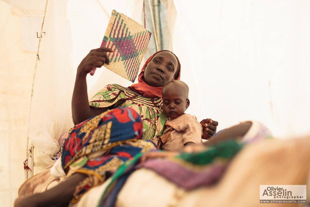 A woman uses a fan to cool off as she lies on a bed next to her twin boys, who are recovering from malnutrition, at a UNICEF-sponsored therapeutic feeding center at the Mongo hospital in the town of Mongo, Guera province, Chad on Tuesday October 16, 2012.