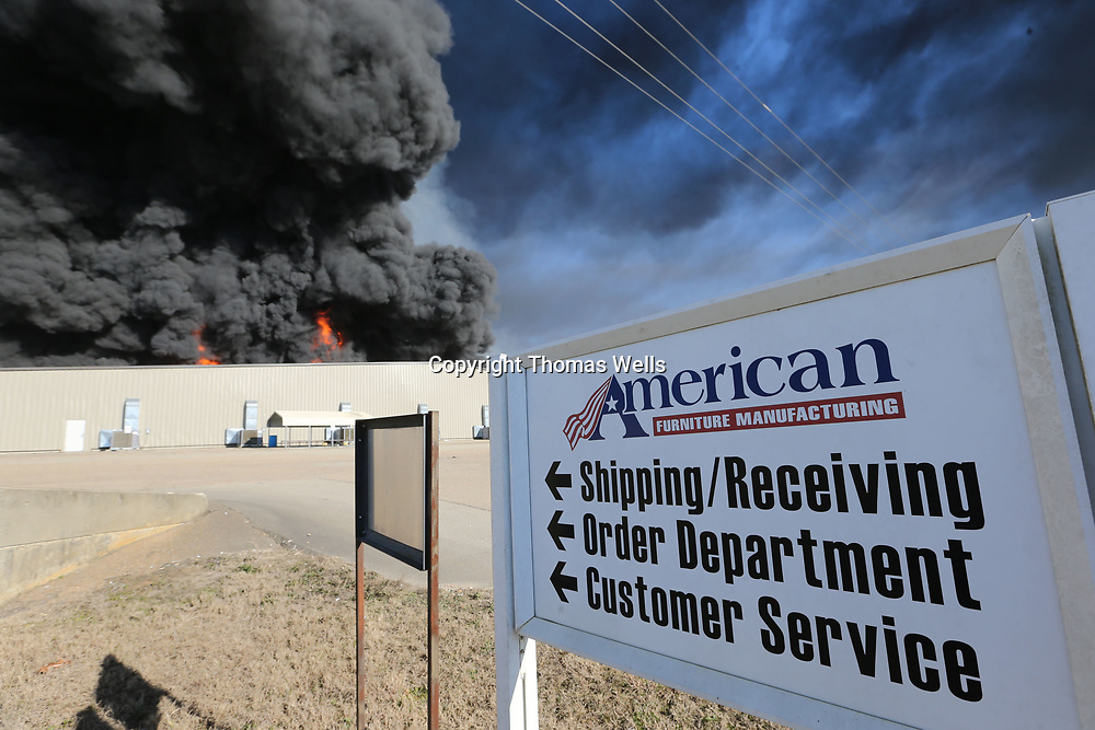 Smoke and flames begin to pour out of the roof as the fire begins to reach the southern wall of American Furniture in Ecru Friday morning.