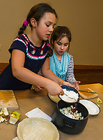 Faith and Mattie add flour and sugar to their apples during Gilford Library's pie making activity on Tuesday.  (Karen Bobotas/for the Laconia Daily Sun)