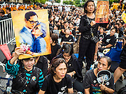 26 NOVEMBER 2016 - BANGKOK, THAILAND: People hold up portraits of the late king of Thailand on Yaowarat Road. Thousands of people gathered in the heart of Bangkok's Chinatown to honor Bhumibol Adulyadej, the Late King of Thailand. The event was organized by the Thai-Chinese community and included a performance by the Royal Thai Navy orchestra of music composed by the Late King, a prayer by hundreds of Buddhist monks. It concluded with a candlelight vigil. The King died after a long hospitalization on October 13. The government has declared a one year mourning period. HRH Crown Prince Maha Vajiralongkorn, the Heir Apparent and Late King's son, is expected to be name the King next week. He will be known as Rama X.       PHOTO BY JACK KURTZ