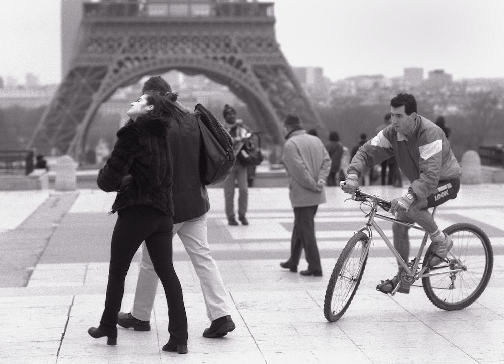 Man on bicycle and couple walking on esplanade, Palais de Chaillot
