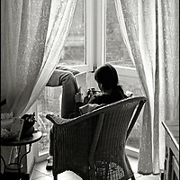 A young woman relaxing in a whicker chair by a window