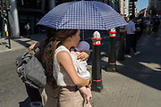 A mother carries her child beneath an umbrella during the 2018 heatwave in the City of London, the capital's historic financial district, on 2nd August 2018, in London, England.