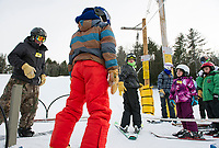 Skiers and riders in the rope tow loading area for an evening of skiing and riding at the Abenaki Ski Area in Wolfeboro.   (Karen Bobotas/for the Laconia Daily Sun)