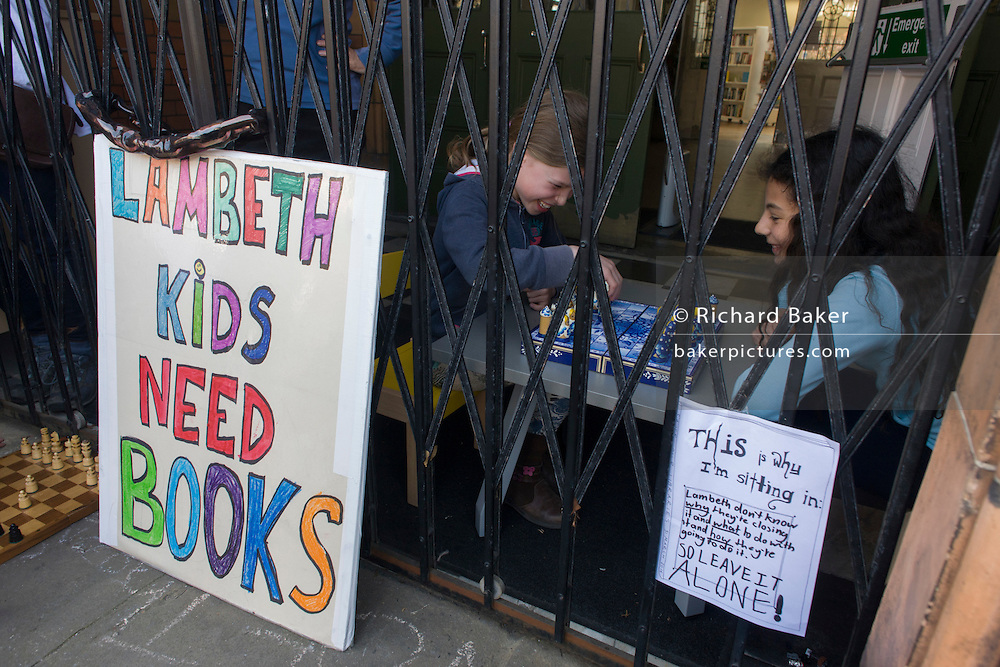 London, UK 2nd April: Young occupiers campaigning aginst the closure by Lambeth council of Carnegie Library play board games inside the front gates in Herne Hill, south London on 2nd April 2016. The angry local community in the south London borough have occupied their important resource for learning and social hub for the weekend. After a long campaign by locals, Lambeth have gone ahead and closed the library's doors for the last time because they say, cuts to their budget mean millions must be saved. A gym will replace the working library and while some of the 20,000 books on shelves will remain, no librarians will be present to administer it. London borough's budget cuts mean four of its 10 libraries will either close, move or be run by volunteers. ©Richard Baker / Alamy Live News.