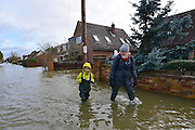 © Licensed to London News Pictures. 09/02/2014. Wraysbury, UK. People wade through the rising water.  Flooding in Wraysbury in Berkshire today 9th February 2014 after the River Thames burst its banks. Photo credit : Stephen Simpson/LNP