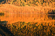 Alaska. Bright fall colors reflecting against Mirror Lake.
