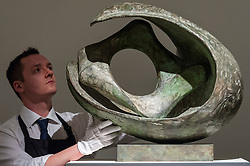 "© Licensed to London News Pictures. 18/11/2016. London, UK. A technician examines ""Curved Form With Inner Form (Anima)"" by Dame Barbara Hepworth (est. GBP500-700k)"", at the preview at Sotheby's of works on view at four upcoming November auctions featuring Modern & Post-War British Art, A Painter's Paradise (Julian Trevelyan & Mary Fedden at Durham Wharf), Scottish Art and Picasso Ceramics from the Lord & Lady Attenborough Private Collection. Photo credit : Stephen Chung/LNP"