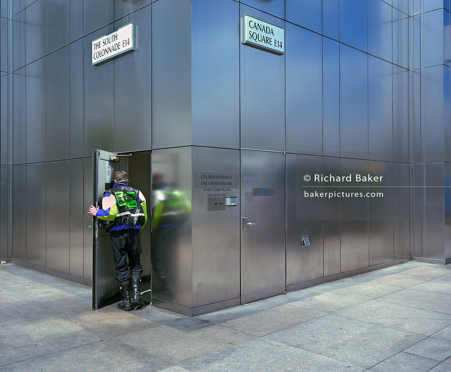 Motorcycle courier enters a corner side door at rear of 1 Canada Square (Canaray Wharf) in London Docklands.