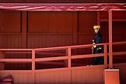 A staffer dressed in traditional attire walks toward the Seiden main hall at  Shuri-jo Castle in Naha, Okinawa Prefecture, Japan, on June 24, 2012. Photographer: Robert Gilhooly