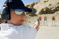 Woan aiming hand gun at firing range