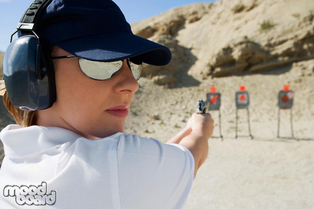 Woan aiming hand gun at firing range