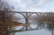 The Symmetrical Reflection of a Roadway Bridge on a Misty Late Autumn Morning Over The Little Miami River in Southwestern Ohio, USA