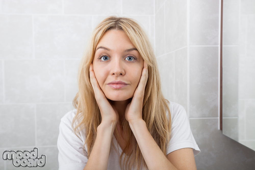 Portrait of young woman touching cheeks in bathroom