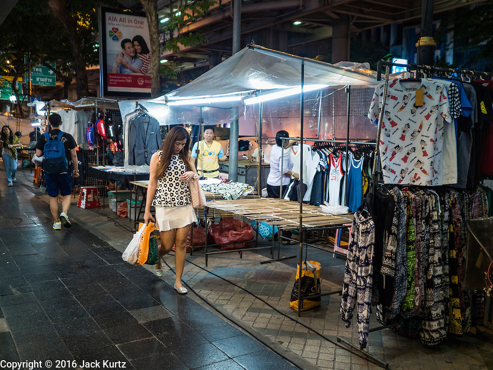 26 MAY 2016 - BANGKOK, THAILAND: A woman walks through the Silom Road night market. The night market on Silom Road, close to Bangkok's famous Patpong tourist area, is being closed by the Bangkok municipal government. Vendors have been told they have to leave the sidewalk on Silom Road by the end of May, 2016. The market is the latest street market being shut down by city officials as a part of the government's plan to clean up Bangkok. The Silom Road night market sells mostly tourist oriented clothes, inexpensive Thai art, and bootleg movies on DVD.       PHOTO BY JACK KURTZ