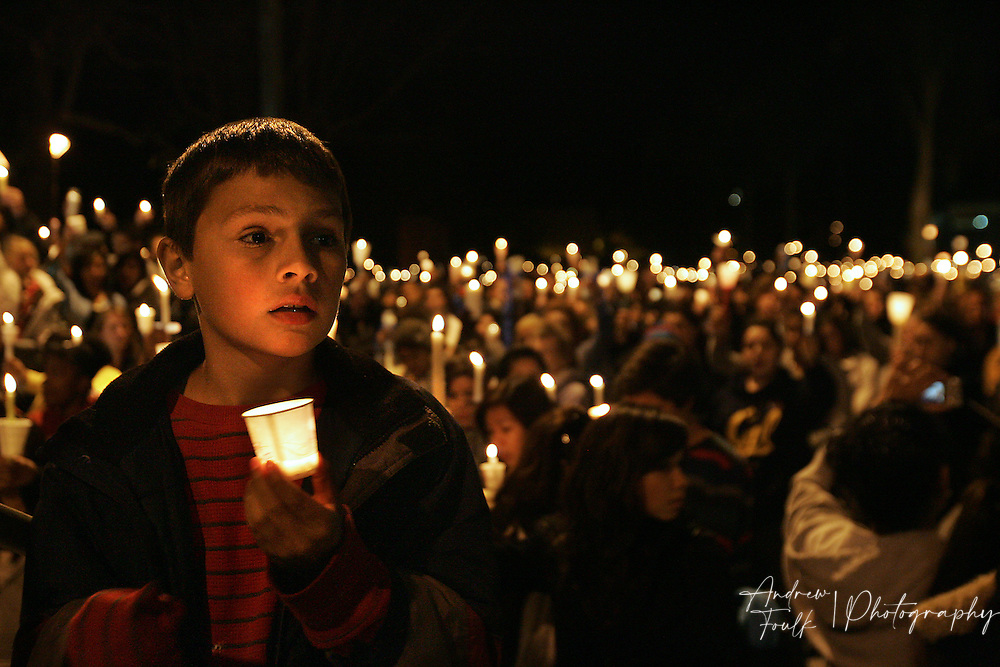 "/Andrew Foulk/ For the North County Times/  .Marcos Gervasio, 9, holds a candle as a sea of around thousand people sing ""Amazing Grace"" in remembrance of Amber Dubois behind him during a Vigil in her honor at Escondido High School Monday night."