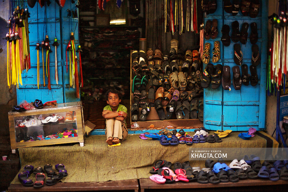 A child waiting for a customer at his shoe shop in Pushkar.<br /> <br /> Holy town of Pushkar, 14 kms from Ajmer is famous for its annual camel fair held in the autumn. With a scared lake, old temples and roof top restaurants, its a major tourist attraction attracting mostly foreign tourists. Pushkar also offers a great variety of delicious food. The town that got famous by its colorful camel fair is a very old religious place for Hindu pilgrims.