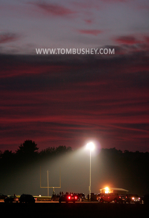 Otisville, NY - Lights shine on a football field as cars start to leave the parking lot after an Orange County Youth Football League game in Otisville on Sept. 14, 2008. Minisink Valley hosted Middletown in the Division 4 game.