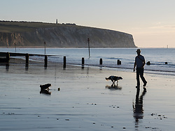 © Licensed to London News Pictures. 23/09/2016. Sandown, Isle of Wight, UK.  A dog walker on the beach at Sandown beach on the Isle of Wight this morning, 23rd September 2016. The day has started cool, but fine and sunny. It will become a little cloudier and breezier later in the South East of England. Photo credit: Rob Arnold/LNP